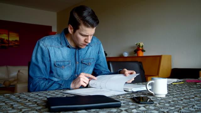Man calculating Bills in Living Room video