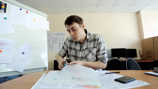 Man carefully cuts carbon paper with black layout of building on it video