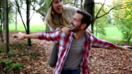 Man carrying girlfriend piggyback in forest video