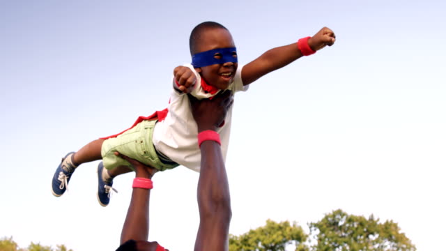 Man carrying his son in costume of superheroes video