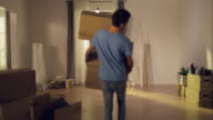 Man carrying moving boxes into new apartment video