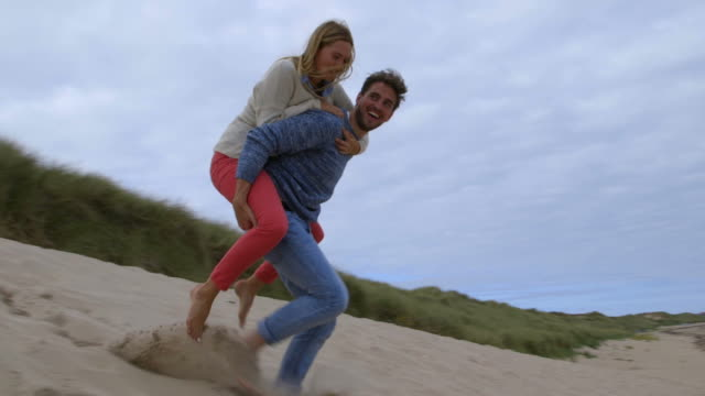 Man carrying woman on his back as they run down sand dunes towards sea in slow motion video