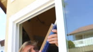 Man Caulks Window Tilt Down video