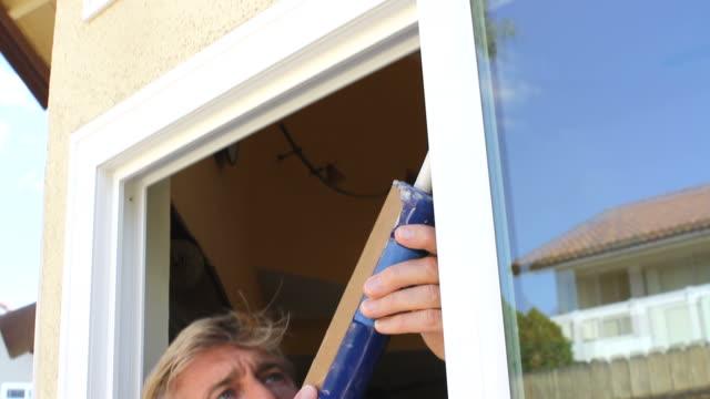 Man Caulks Window Tilt Down video