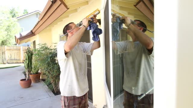 Man Caulks Window video
