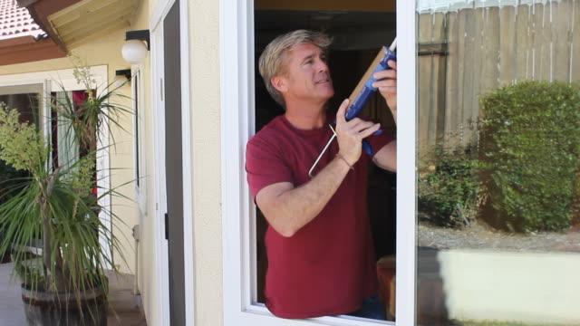 Man Caulks Window MS video