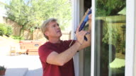 Man Caulks Window WS video