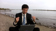 Man celebrates success with laptop. video