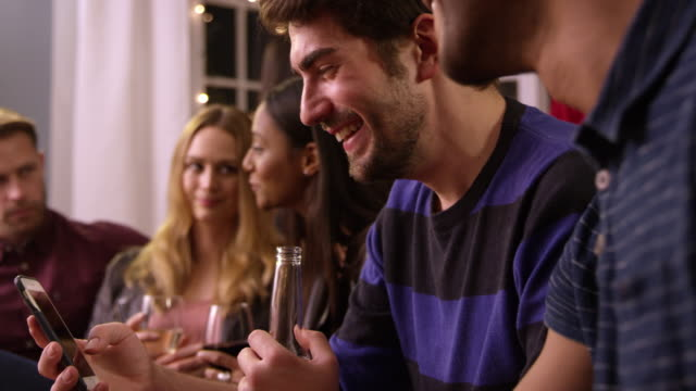 Man Checking Mobile Phone At Party With Friends video