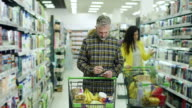 Man checking shopping list in supermarket video