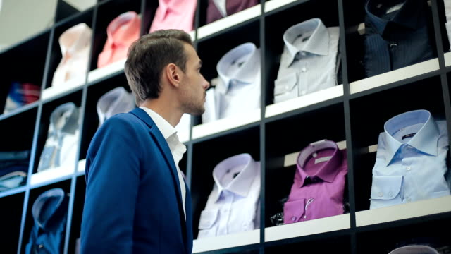 Man chooses a shirt at store video