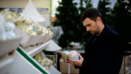 Man chooses Christmas decorations in a shop video