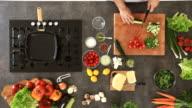 Man chopping cucumber on cutting board, preparing vegetable salad video
