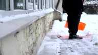 Man clean snow with a shovel in winter time. FullHD video