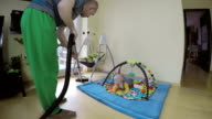 man cleaning floor with hoover and curious baby on play mat. video
