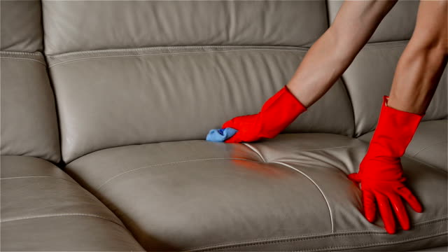 man cleaning leather sofa at home video