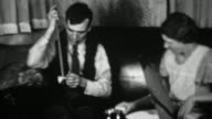 1936: Man cleaning out gun at home while supportive wife watches. video