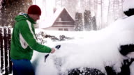 A man clears the snow off the car in the morning after a snowfall video