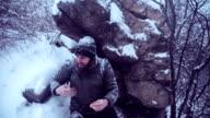 Man climbing snowbound rocks video