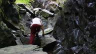 Man climbs rocks in slow motion video