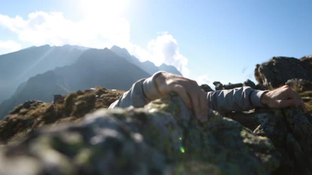 Man climbs to rock crest sun sets behind mountain range video