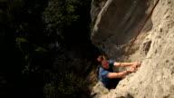 Man climbs vertical rock cliff, to belayer video
