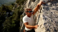 Man climbs vertical rock cliff video