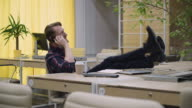 Man closes laptop picks up the phone, throws his feet up on the table video