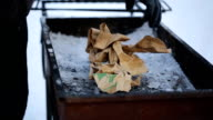 A man collects bonfire of paper of sticks in grill winter video