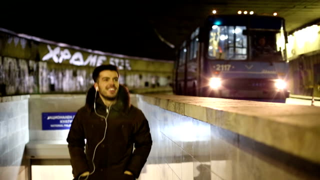Man coming out of the subway and listening to music video
