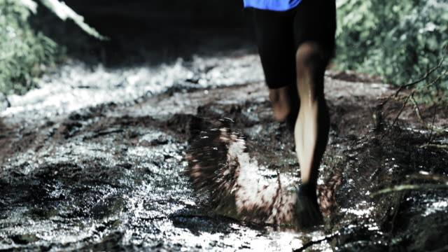 TD Man competing in a night trail run running across a puddle video