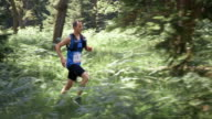 SLO MO DS Man competing in a trail marathon through the forest video