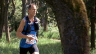 SLO MO DS Man competing in marathon through forest video