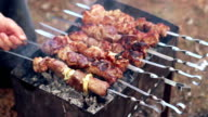 Man cooking marinated shish kebab, meat grilling on metal skewers. video