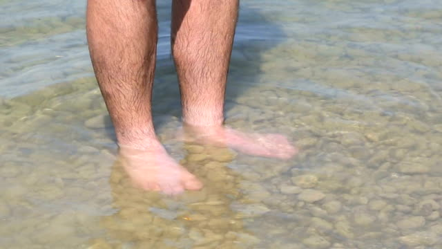 Man cools his feet in a lake video