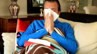 Man coughing and resting in a home video