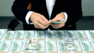 Man counting Many American Dollars. A lot of 100 US dollar bills on table video