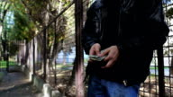 Man counts fake dollars in back park alley. video