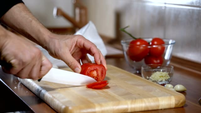 man cuts a tomato for cooking bruschetta video