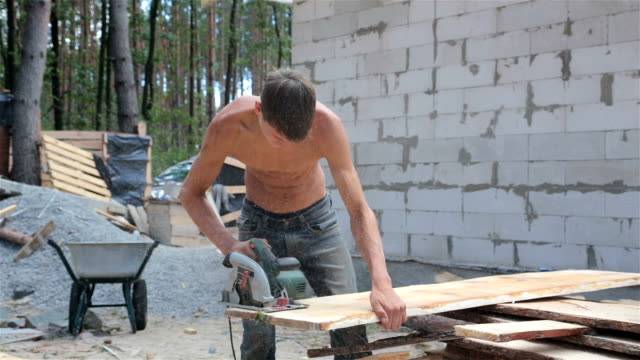 Man cuts a wooden plank with a circular saw. video