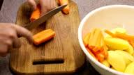 Man cuts carrots on a cutting board video