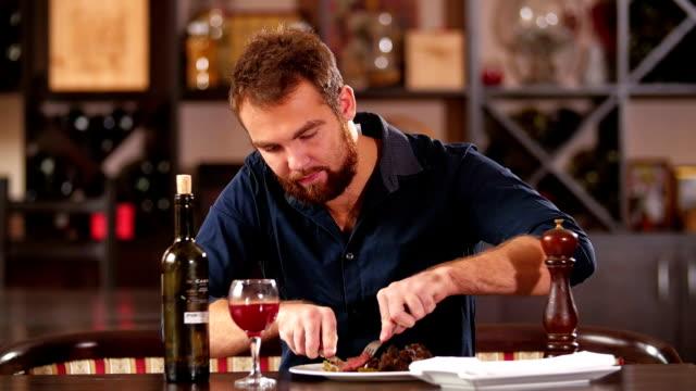 man cuts off a piece of steak close-up video