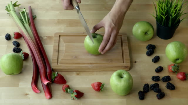 Man cuts the apple into pieces on the kitchen table view from above. video