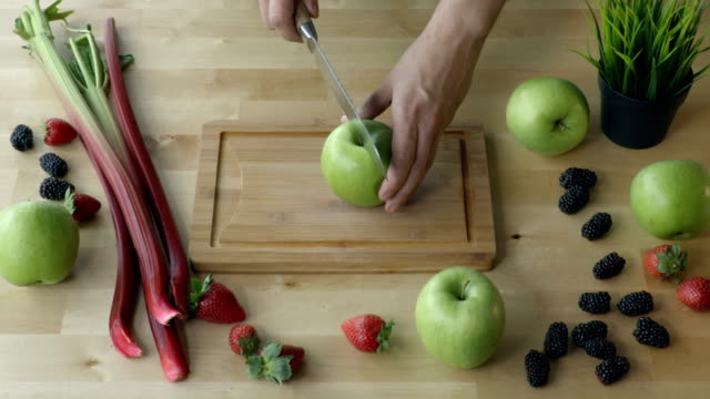 Man cuts the apple on the kitchen table view from above. video