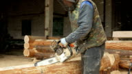 Man cuts wood chainsaw for future home. Protective face mask on the face of the builder and a lot of sawdust. Hangar with a part of the future home on the background video