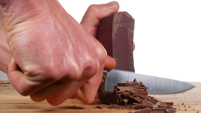 Man Cutting Black Chocolate with Knife, Slow motion 4K video