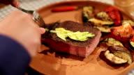Man cutting medium well steak with a knife in restaurant video