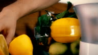 Man cutting whole lemon and making juice with a juicer. FullHD closeup shot video