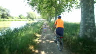 Man cycling beside river with granddaughter video