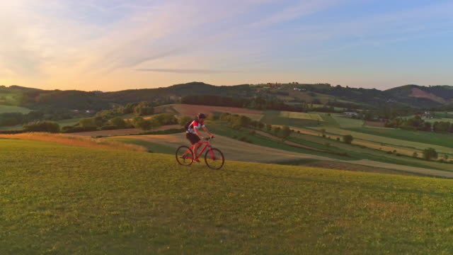 AERIAL SLO MO Man cycling on a hill covered with grass video
